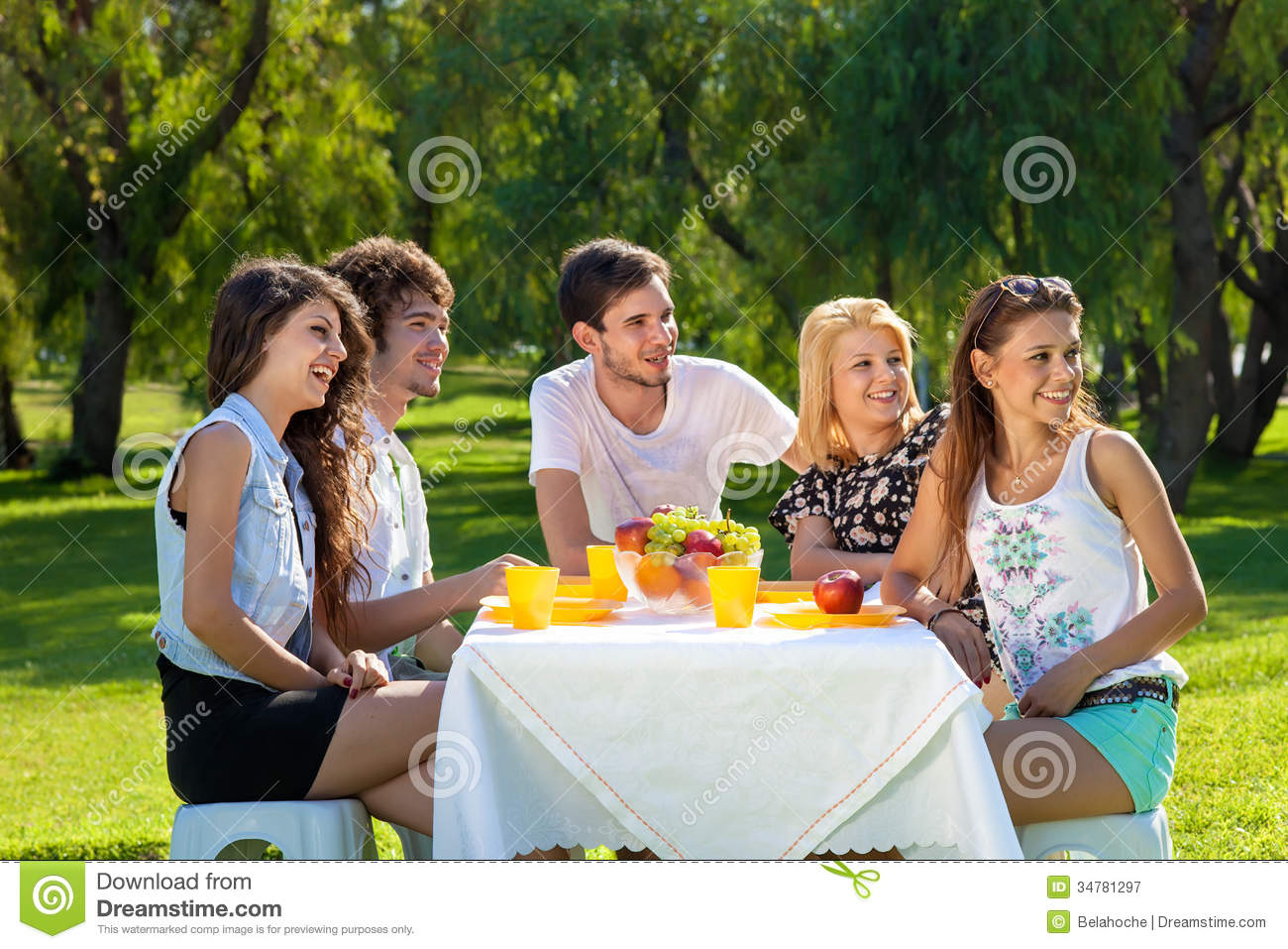 young friends having a picnic outdoors in the park sitting at a table ...