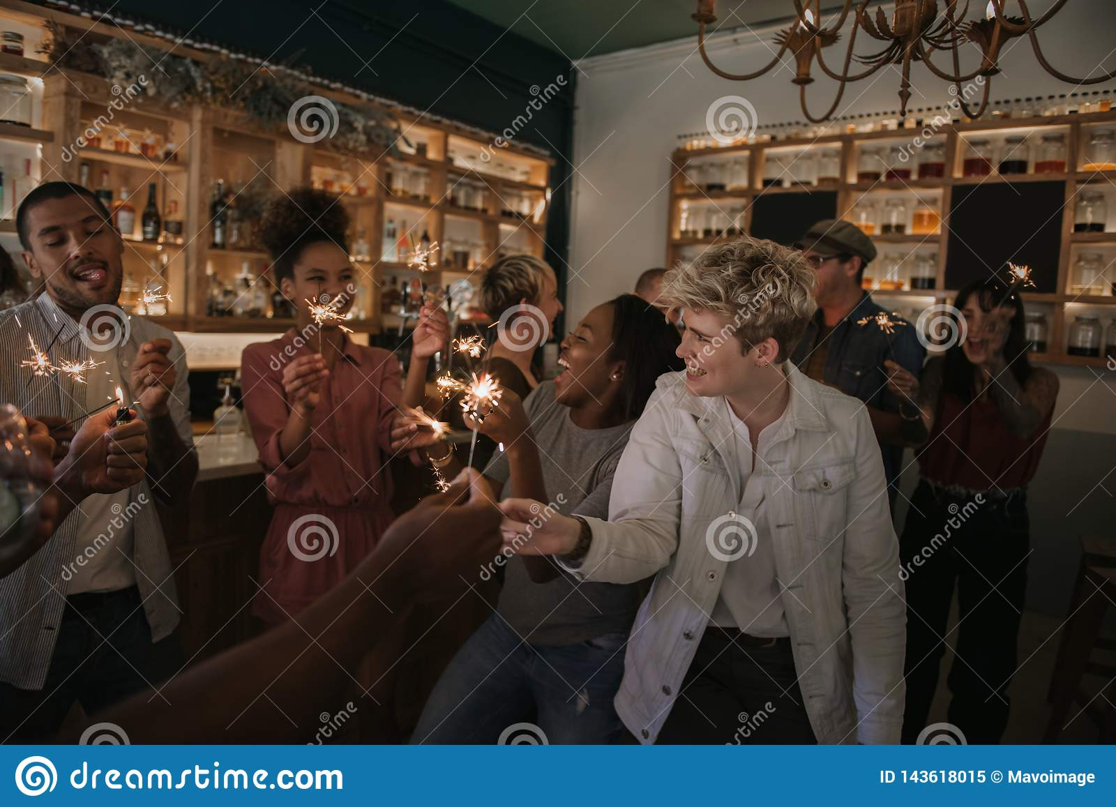 Group of friends celebrating with sparklers in a bar