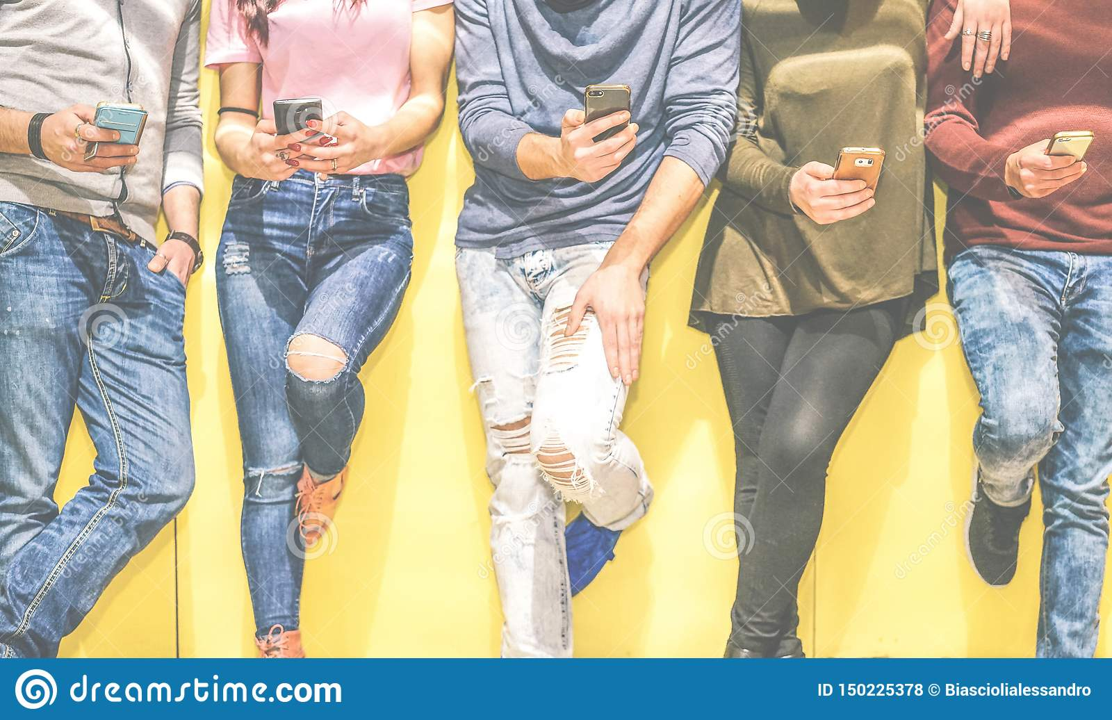 Group of young friends leaning on a wall using mobile phones - Multiracial people connecting on social network with smart phone
