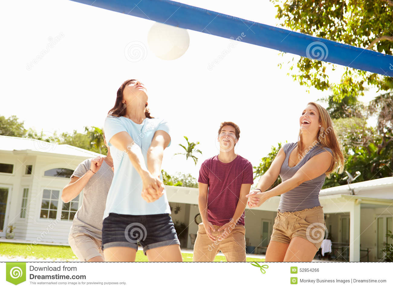 Group Of Young Friends Playing Volleyball Match Stock ...
