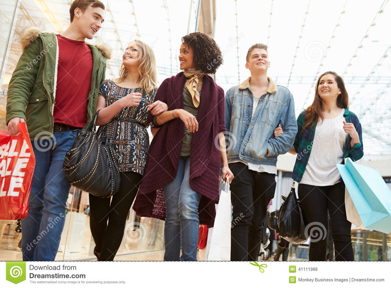Group Of Young Friends Shopping In Mall Together Stock