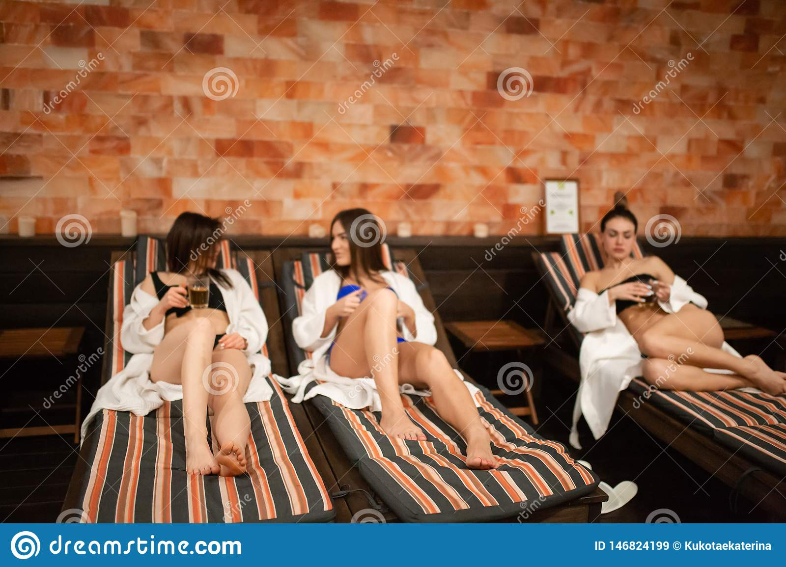 A group of young girls relaxing on a wooden deck in the sauna. Having fun in the female company