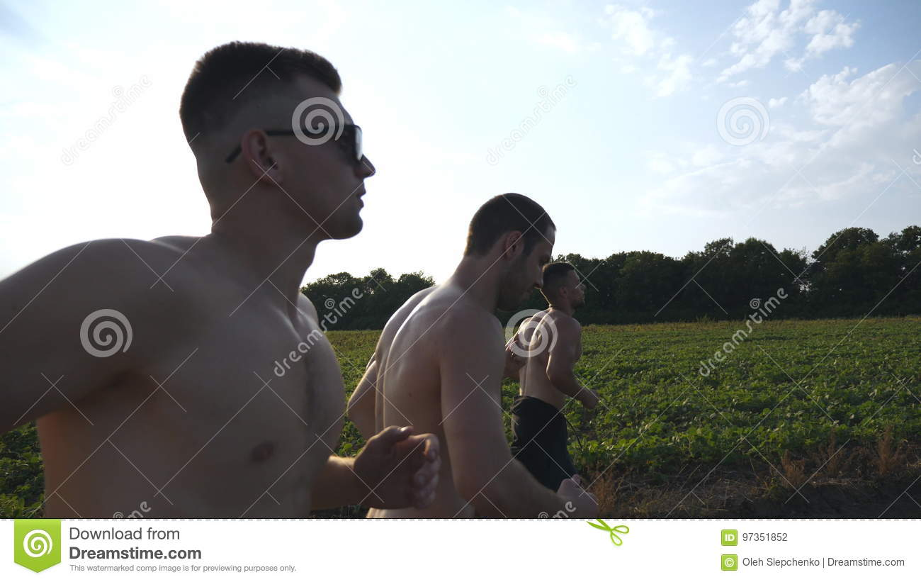 Group of young men running along rural road over field with sun flare at background. Profile of male athletes jogging in
