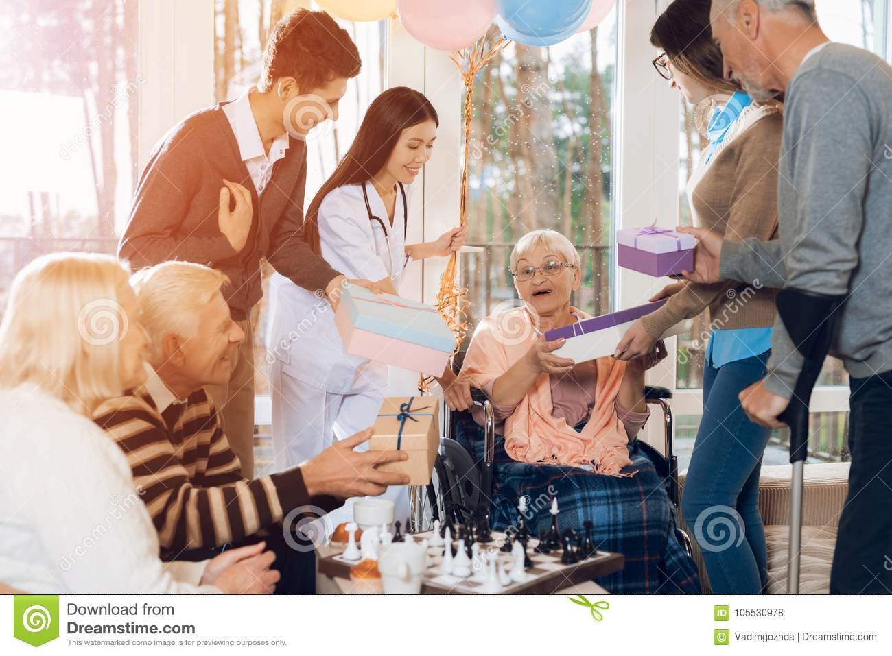 A Group Of Young And Old People In A Nursing Home Congratulate An