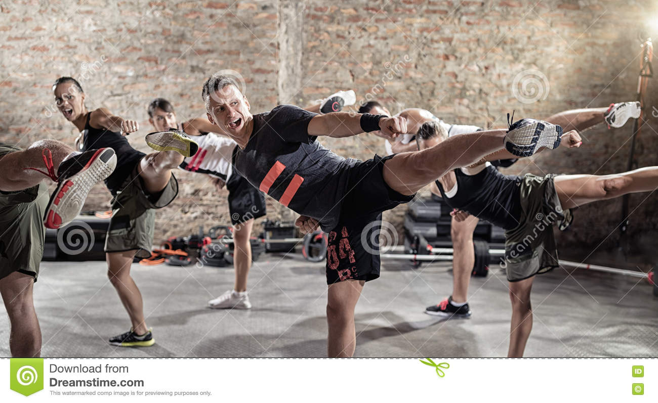 Group of young people doing kick box exercise