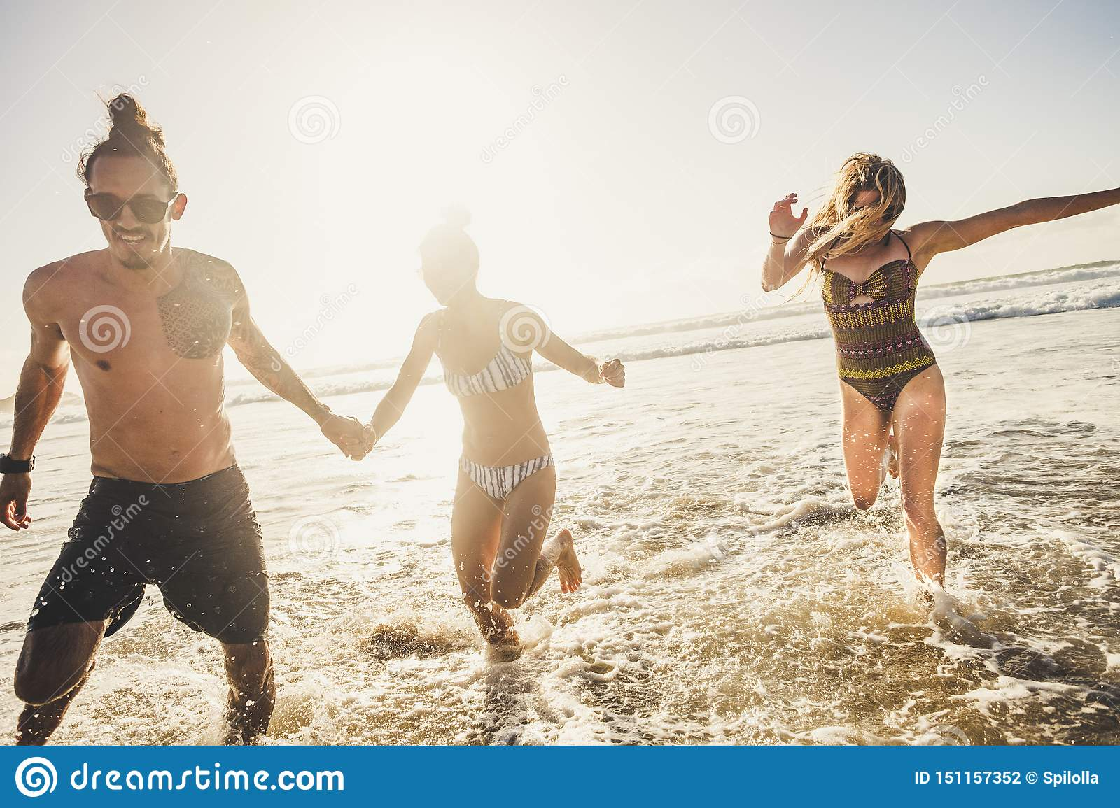Group of young people friends enjoying with fun the summer holiday vacation running at the beach to the water in playful outdoor