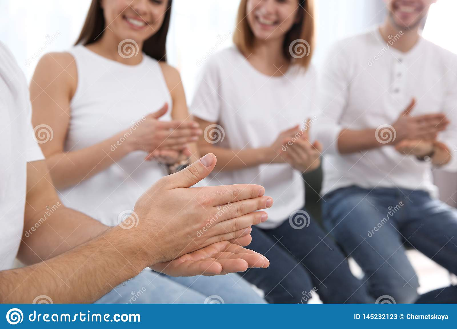 Group of young people learning sign language with teacher indoors