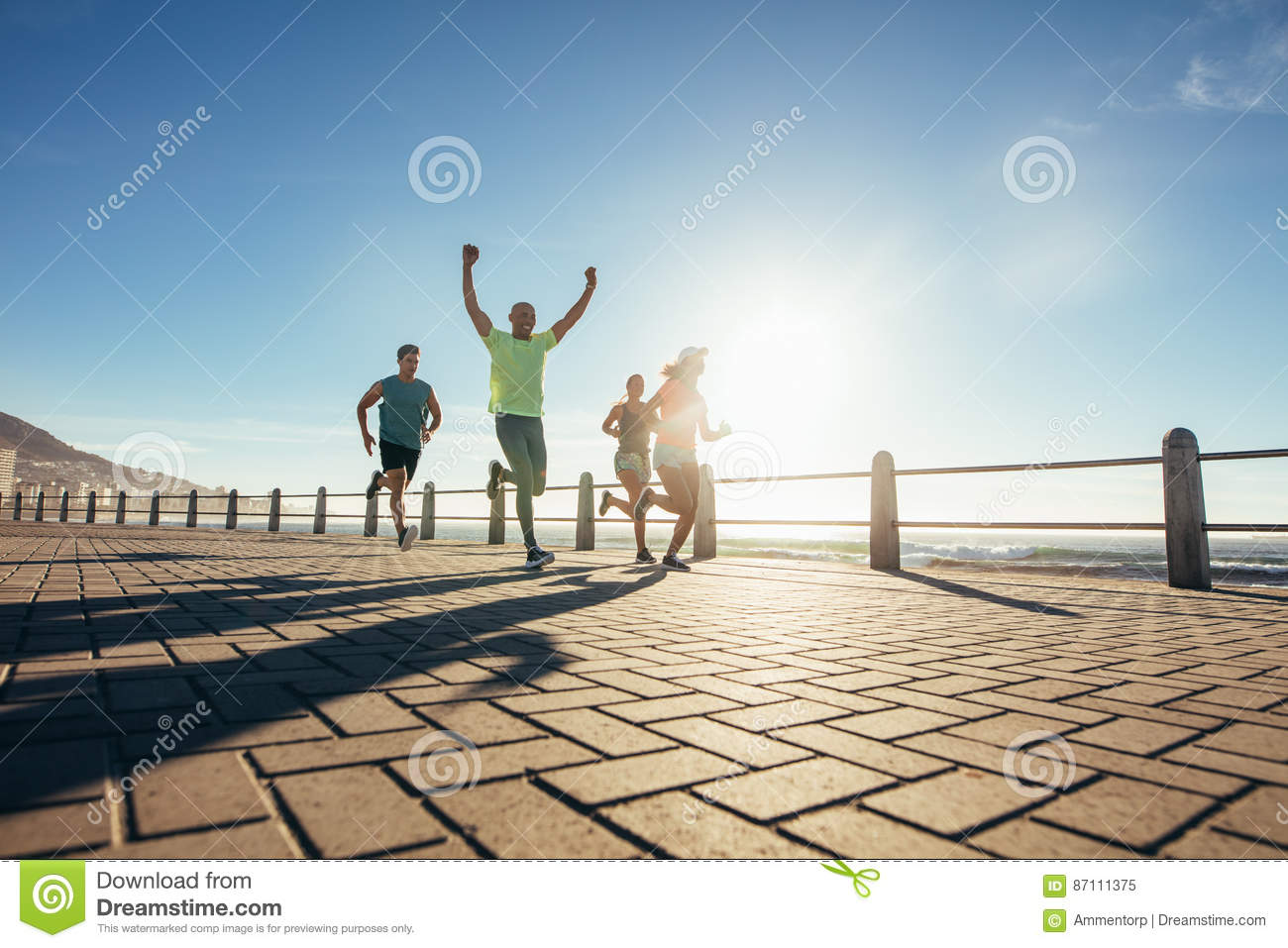 Group of young people running along seaside