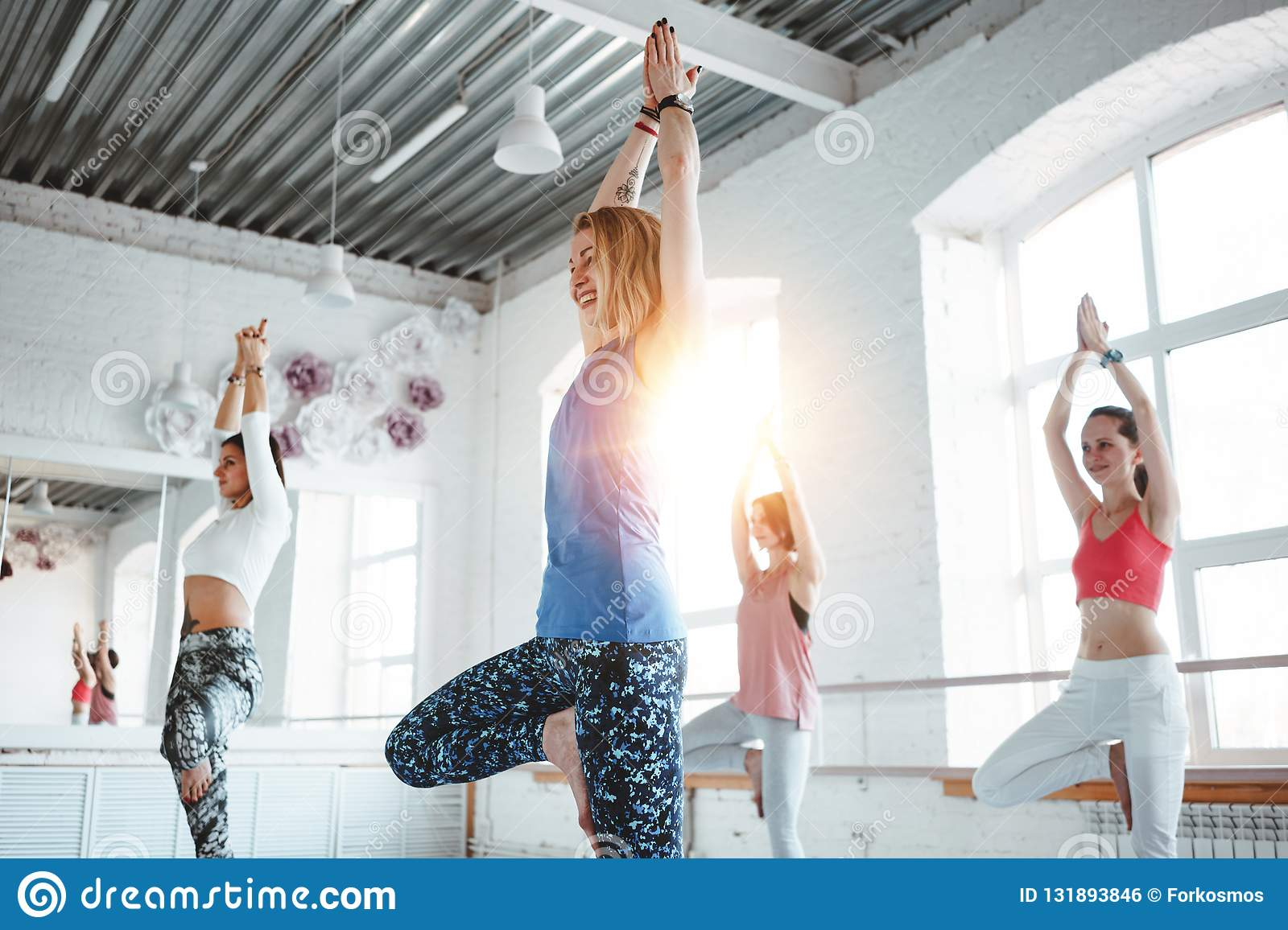 Group of young slim woman practice yoga exercise indoor class. People doing fitness together