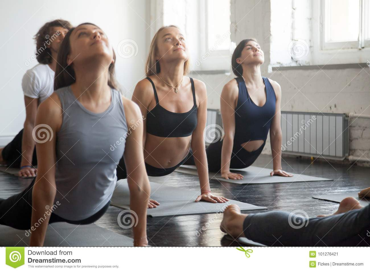 Group of young sporty people in upward facing dog pose
