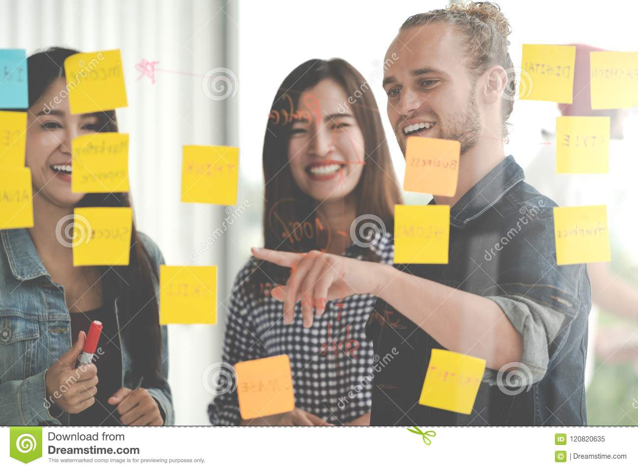 Group of young successful creative multiethnic team smile and brainstorm on project together in modern office with post note or st