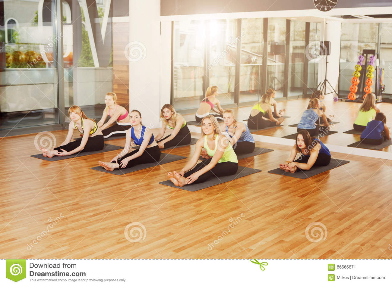 Group of young women in yoga class, stretching