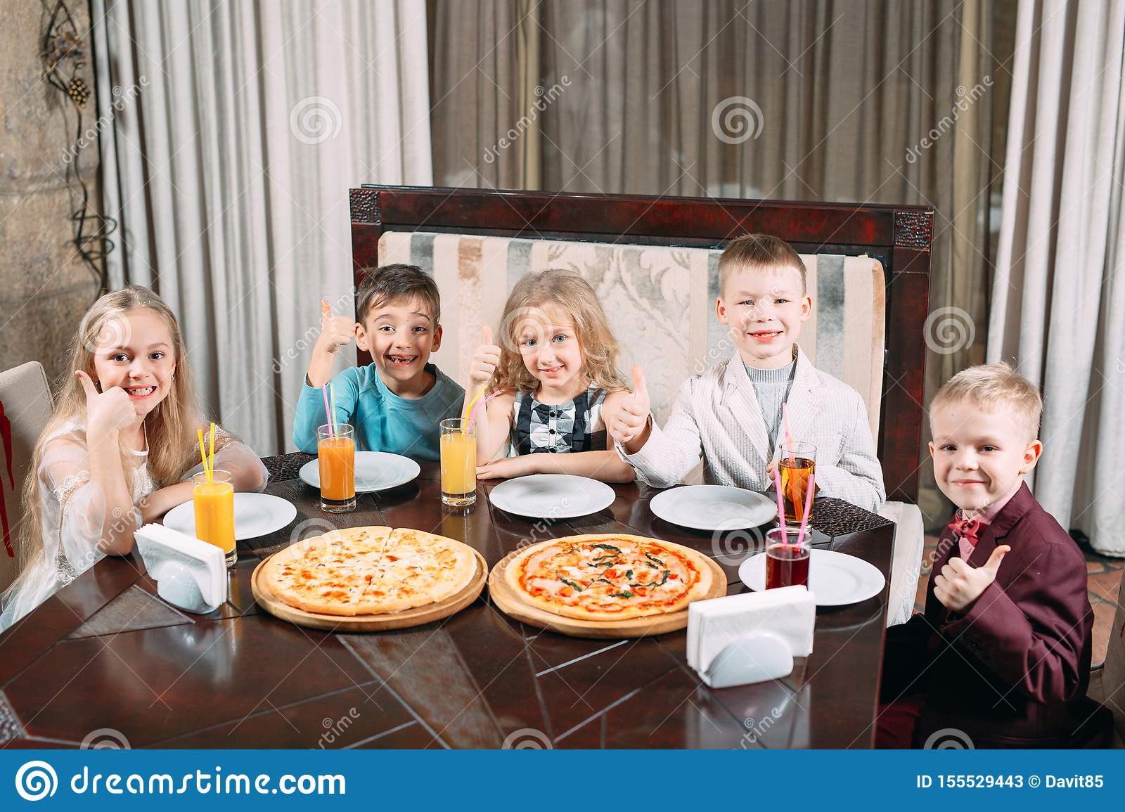 Groupe of Children eat pizza in the restaurant.