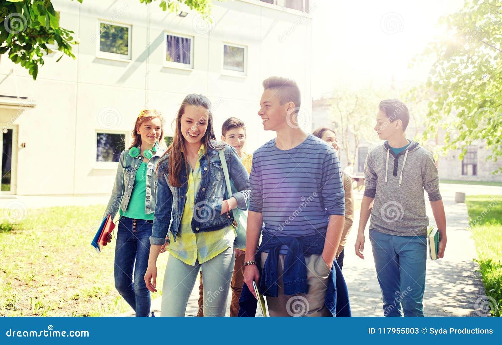 Groupe d étudiants adolescents heureux marchant dehors