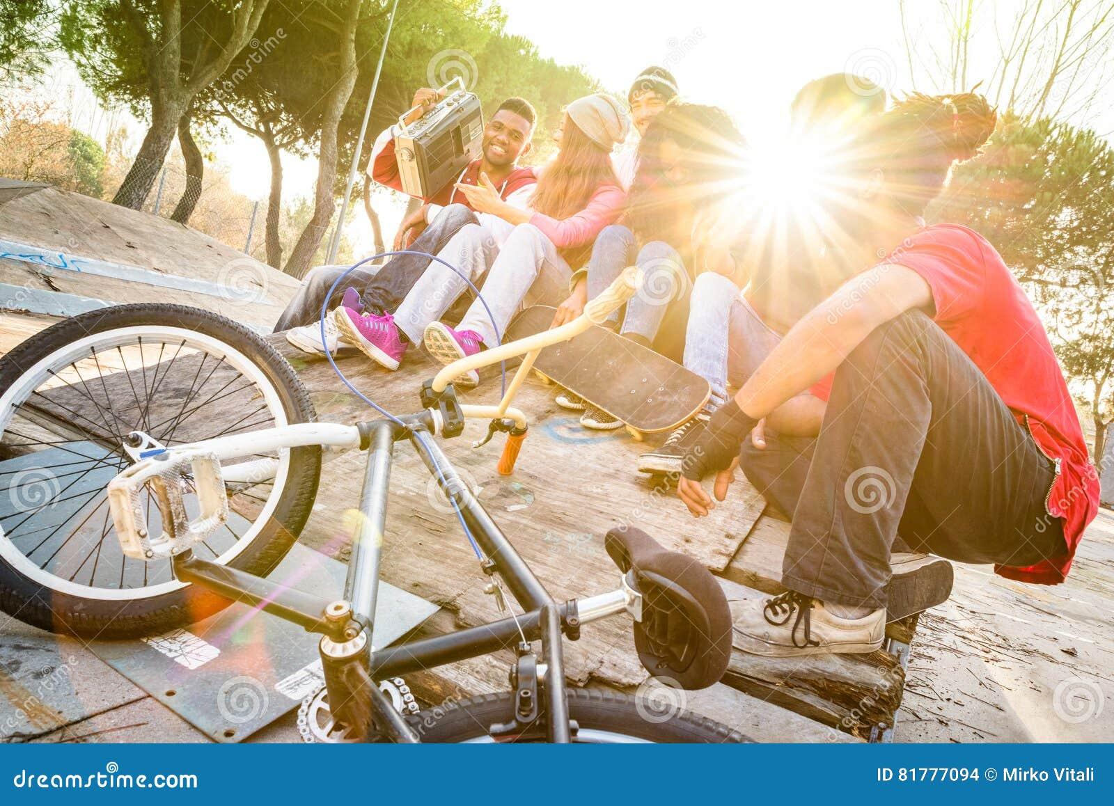Groupe d amis à la mode ayant l amusement ensemble au parc de bmx de patin