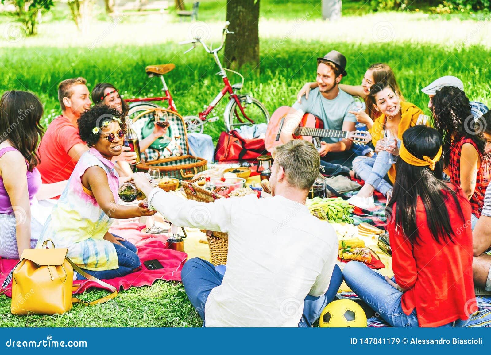 Groupe d amis appréciant un pique-nique tout en mangeant et buvant du vin rouge se reposant sur la couverture en parc extérieur