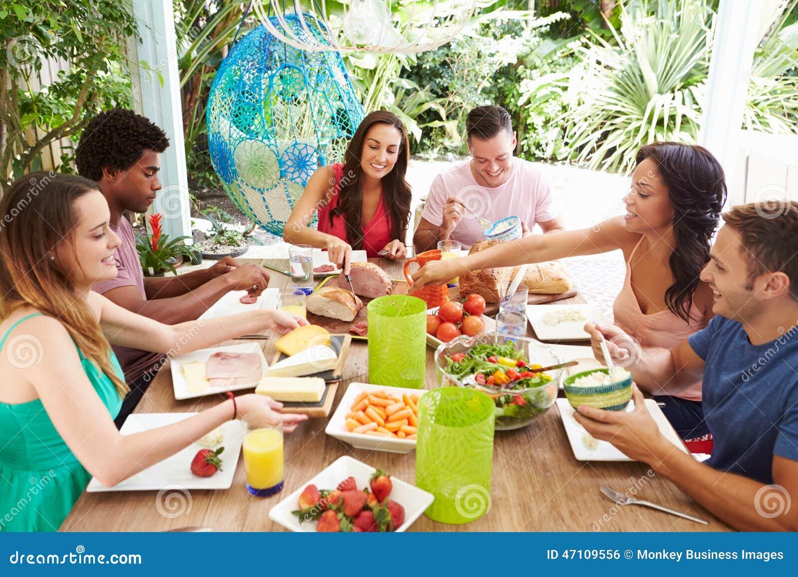 Groupe d 39 amis appr ciant le repas dehors la maison photo for Repas pour amis