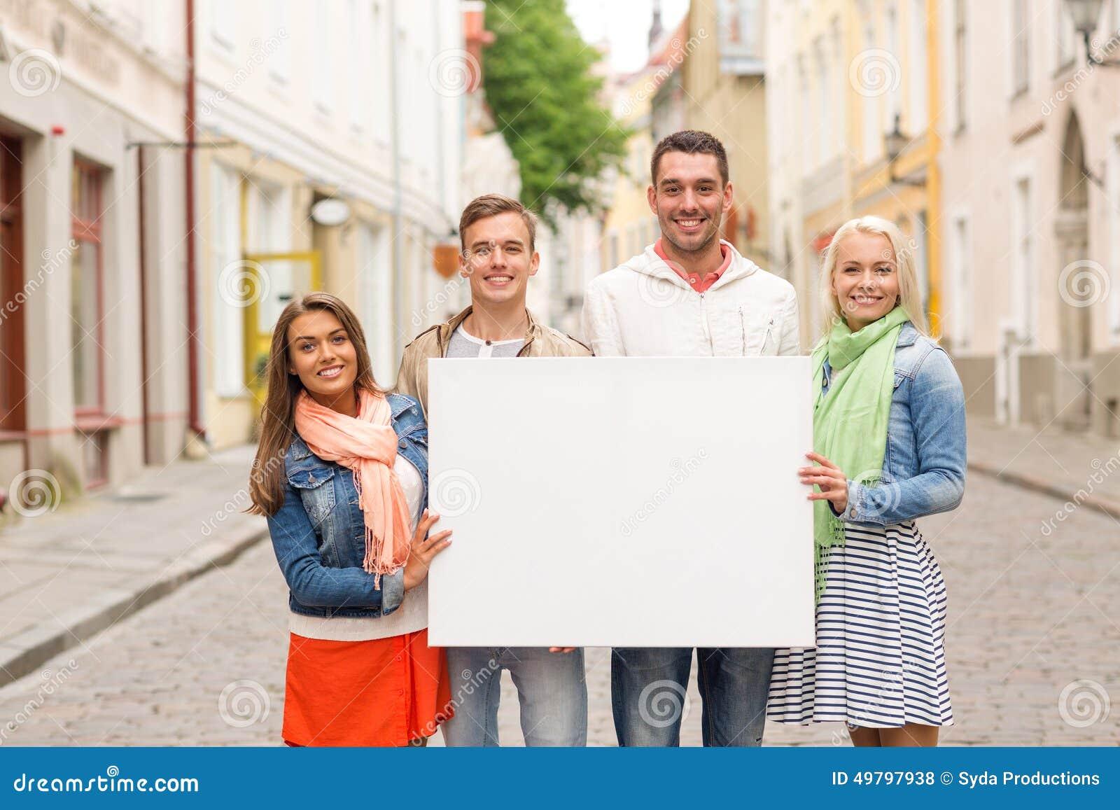 Groupe d amis de sourire avec le conseil blanc vide