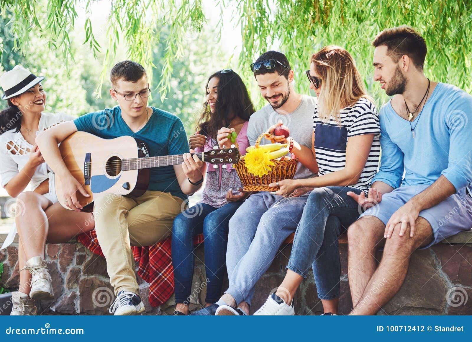 Groupe d amis heureux avec la guitare Tandis que l un d entre eux joue la guitare et d autres lui donnent une salve d applaudisse