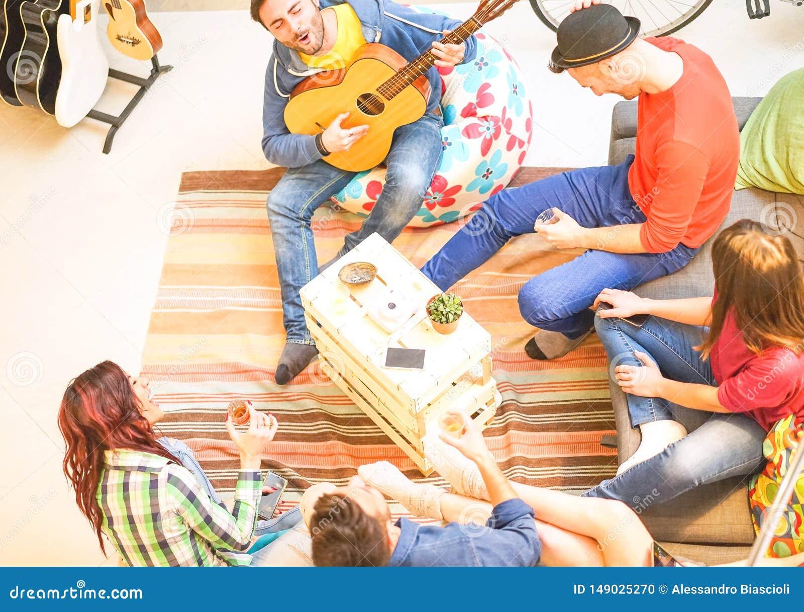Groupe d amis jouant la guitare et buvant la r?union heureuse des jeunes de bi?re et de whiskey ? la maison - dans le salon