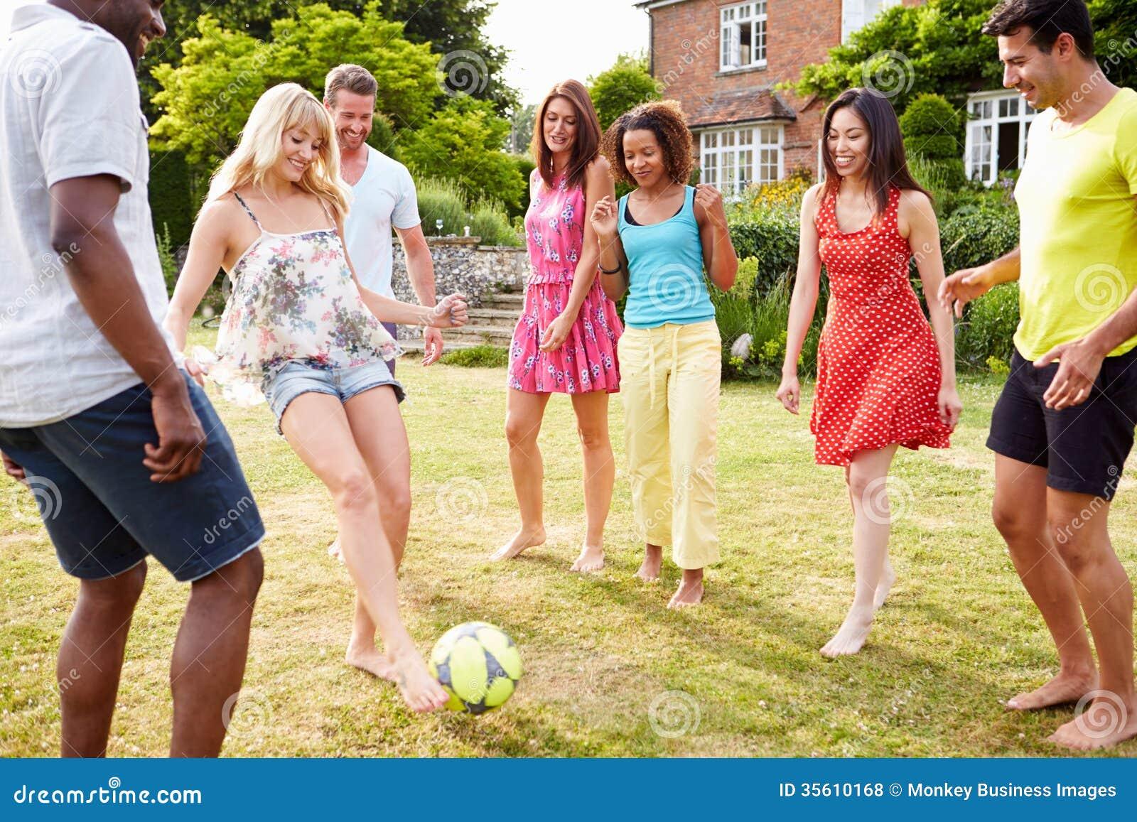 Groupe d amis jouant le football dans le jardin