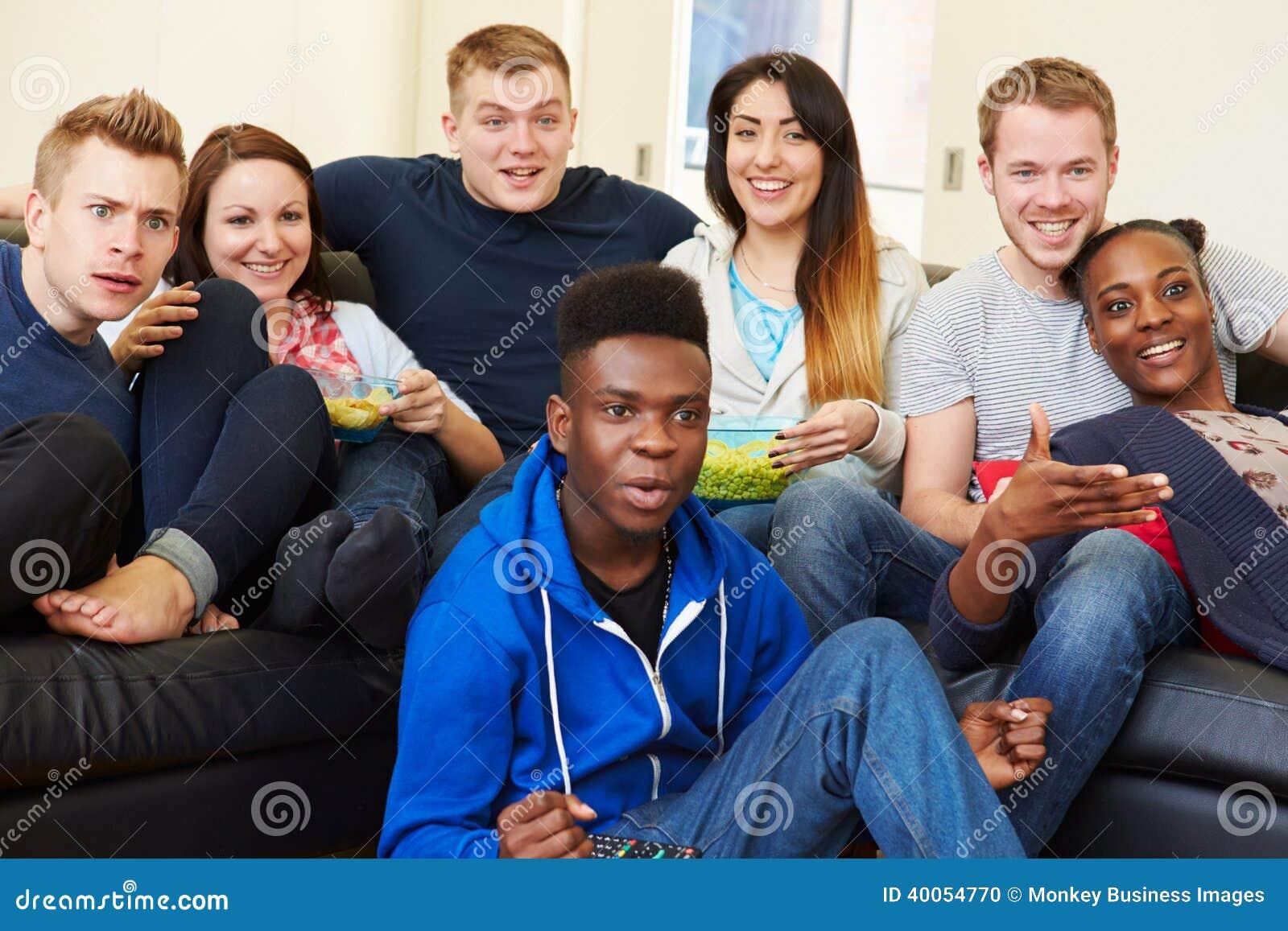 Groupe d amis regardant la télévision à la maison ensemble