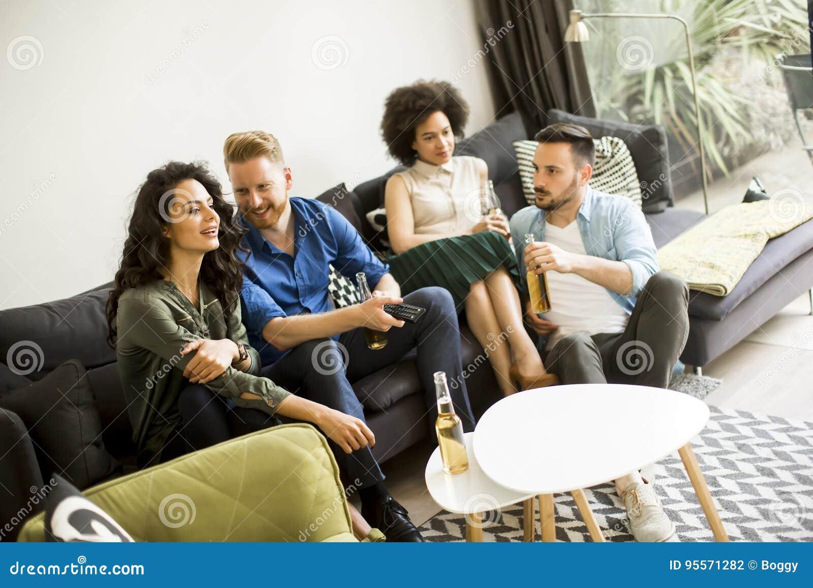 Groupe d amis regardant TV, cidre potable et ayant l amusement