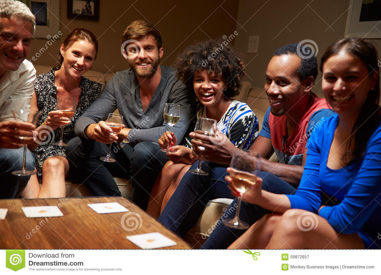 Groupe d amis s asseyant autour d une table à la partie de maison