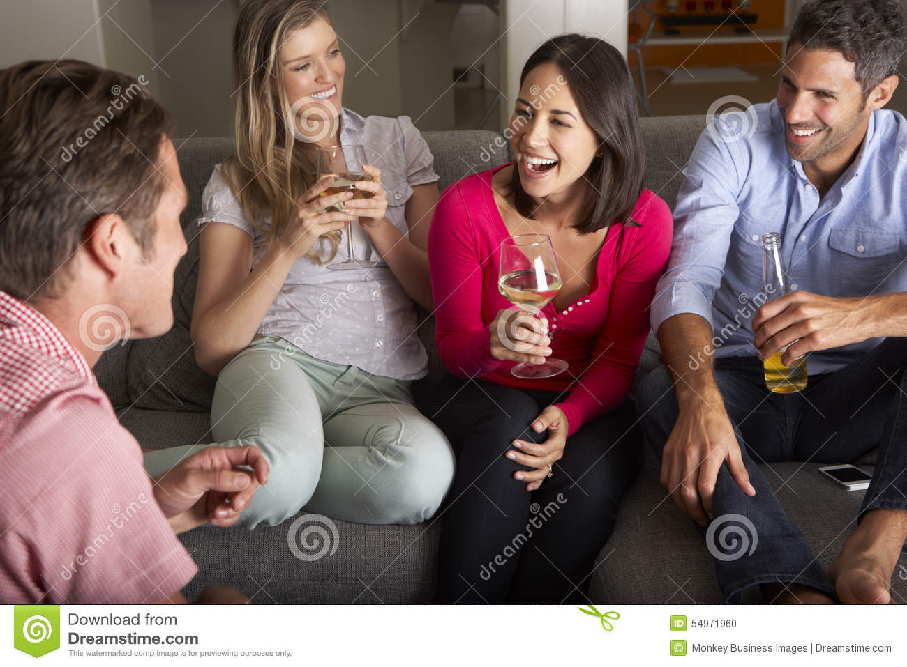Groupe d amis s asseyant sur Sofa Talking And Drinking Wine