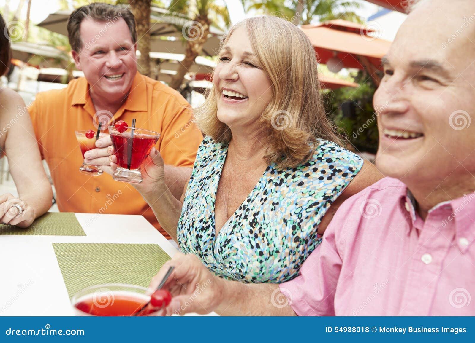 Groupe d amis supérieurs appréciant des cocktails dans la barre ensemble