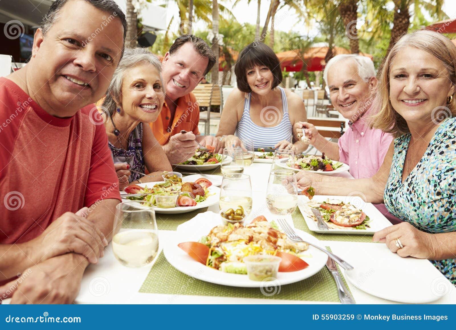 Groupe d amis supérieurs appréciant le repas dans le restaurant extérieur