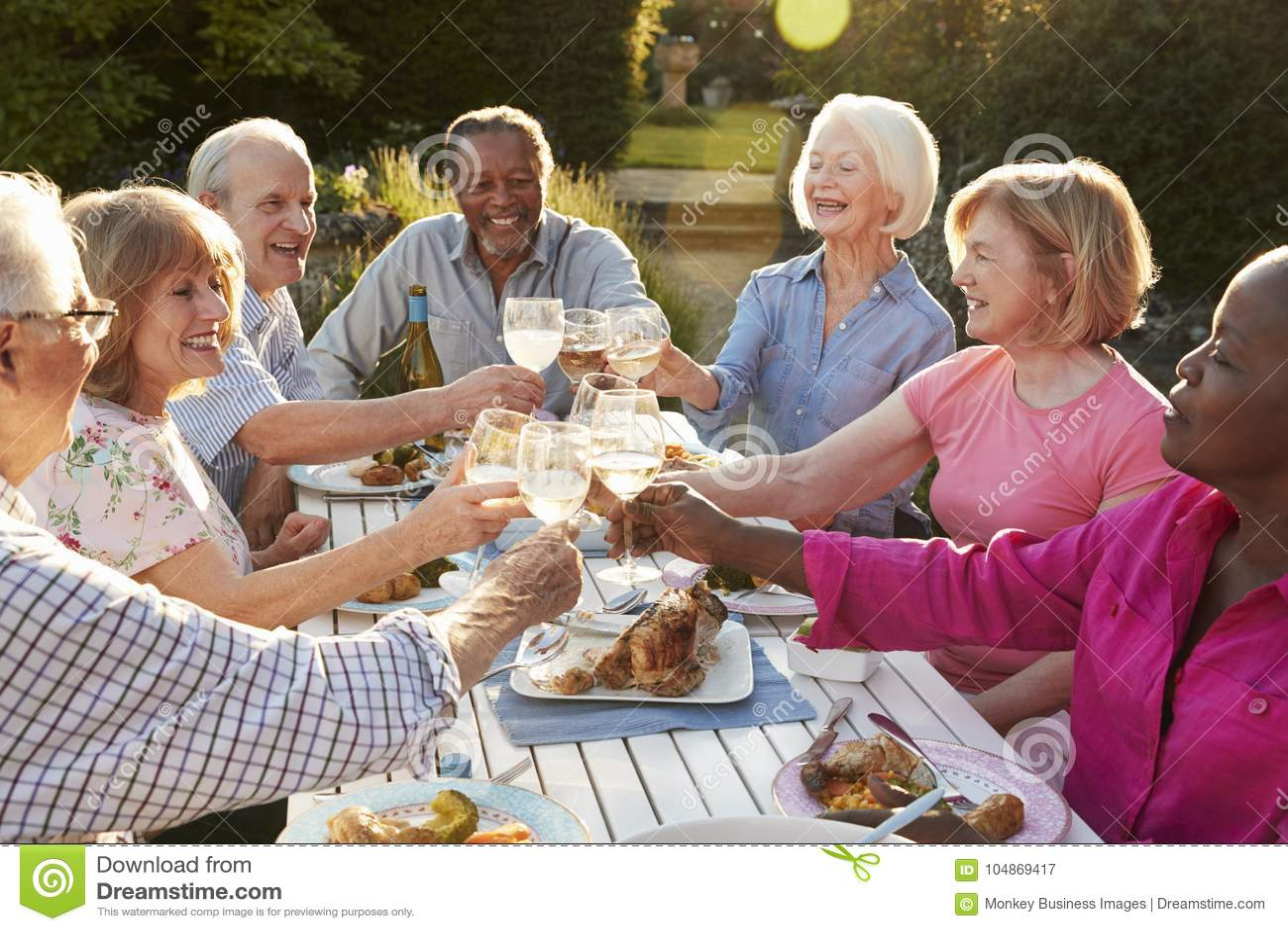 Groupe d amis supérieurs faisant un pain grillé au dîner extérieur