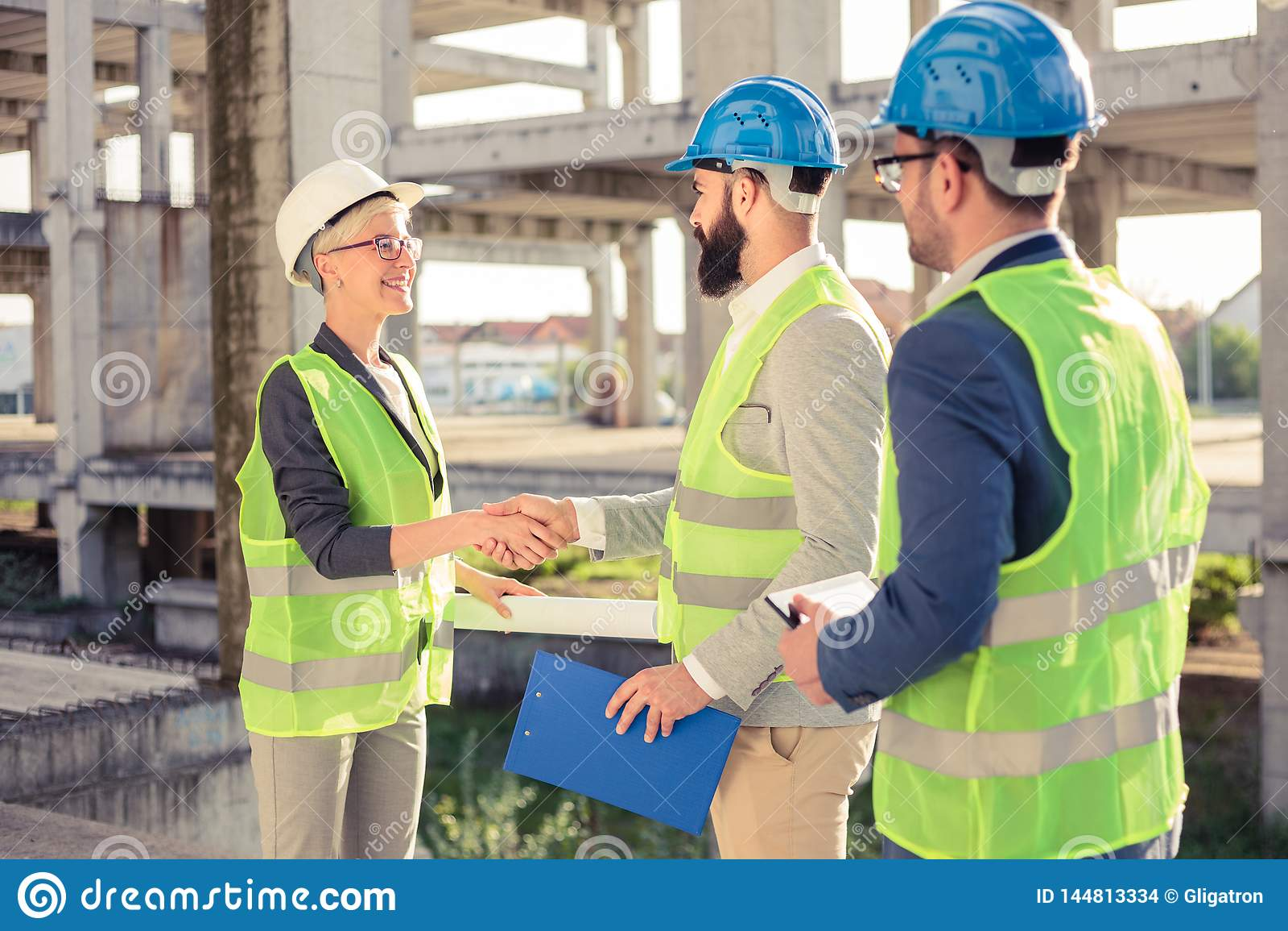 Groupe d architectes ou d associés se serrant la main sur un chantier de construction