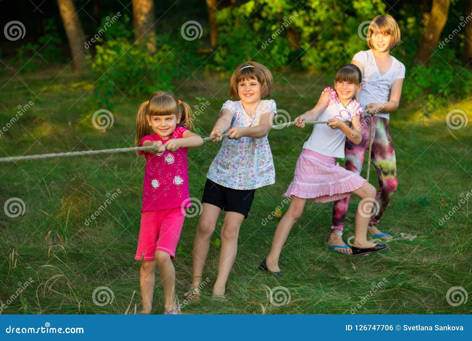 Groupe d enfants heureux jouant le conflit dehors sur l herbe Corde de traction d enfants au parc