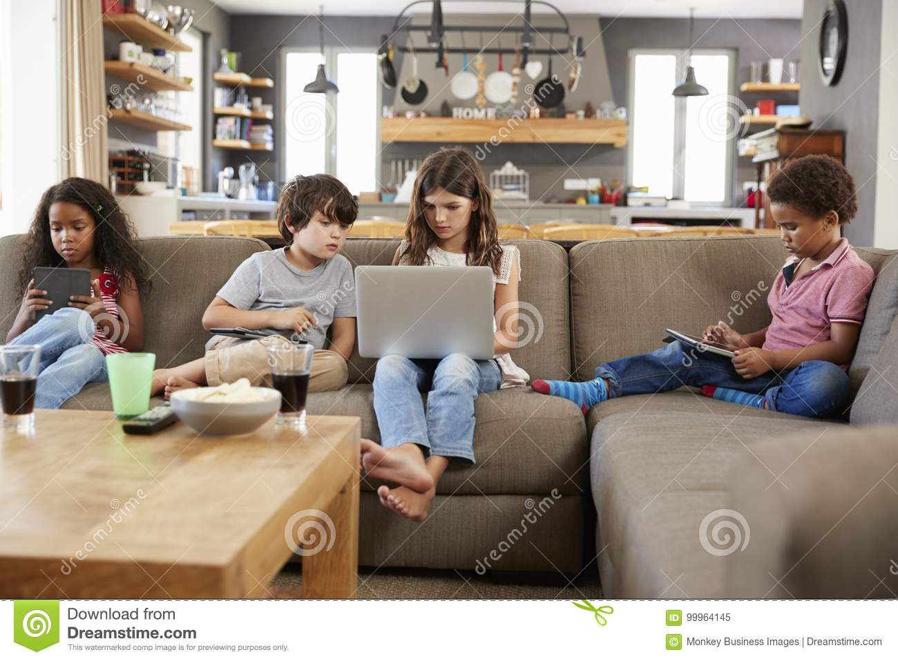 Groupe d enfants s asseyant sur Sofa Using Digital Devices