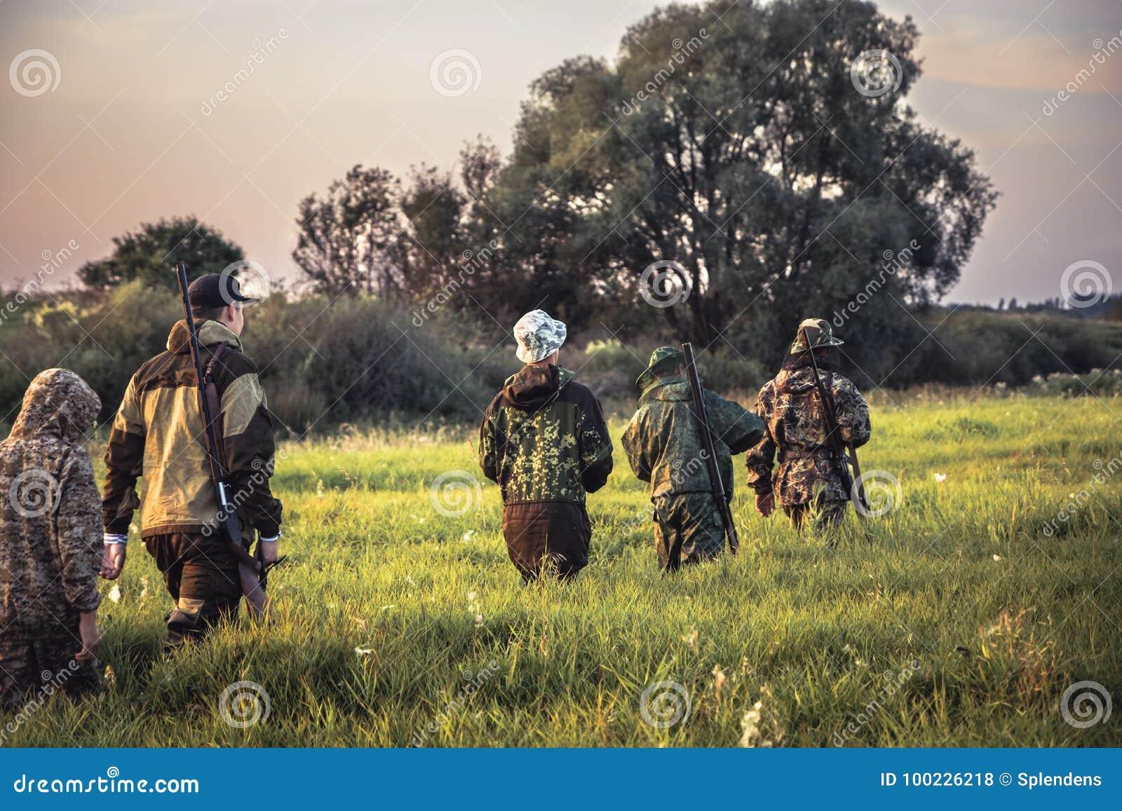 Groupe de chasseurs des hommes passant par l herbe grande sur le champ rural au coucher du soleil pendant la saison de chasse