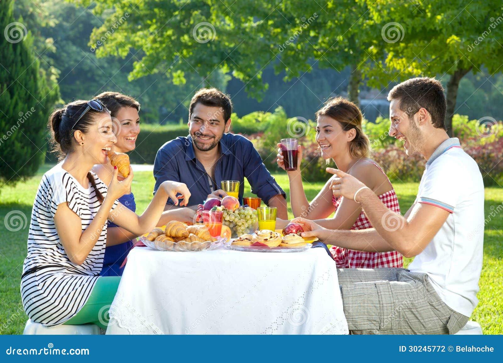 Amis appréciant un repas extérieur sain