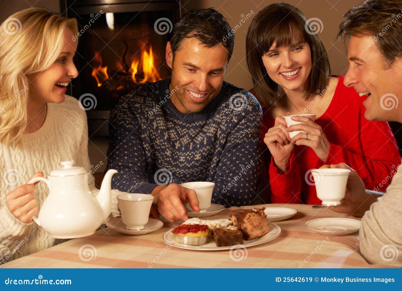 Groupe de couples appréciant le thé et le gâteau ensemble