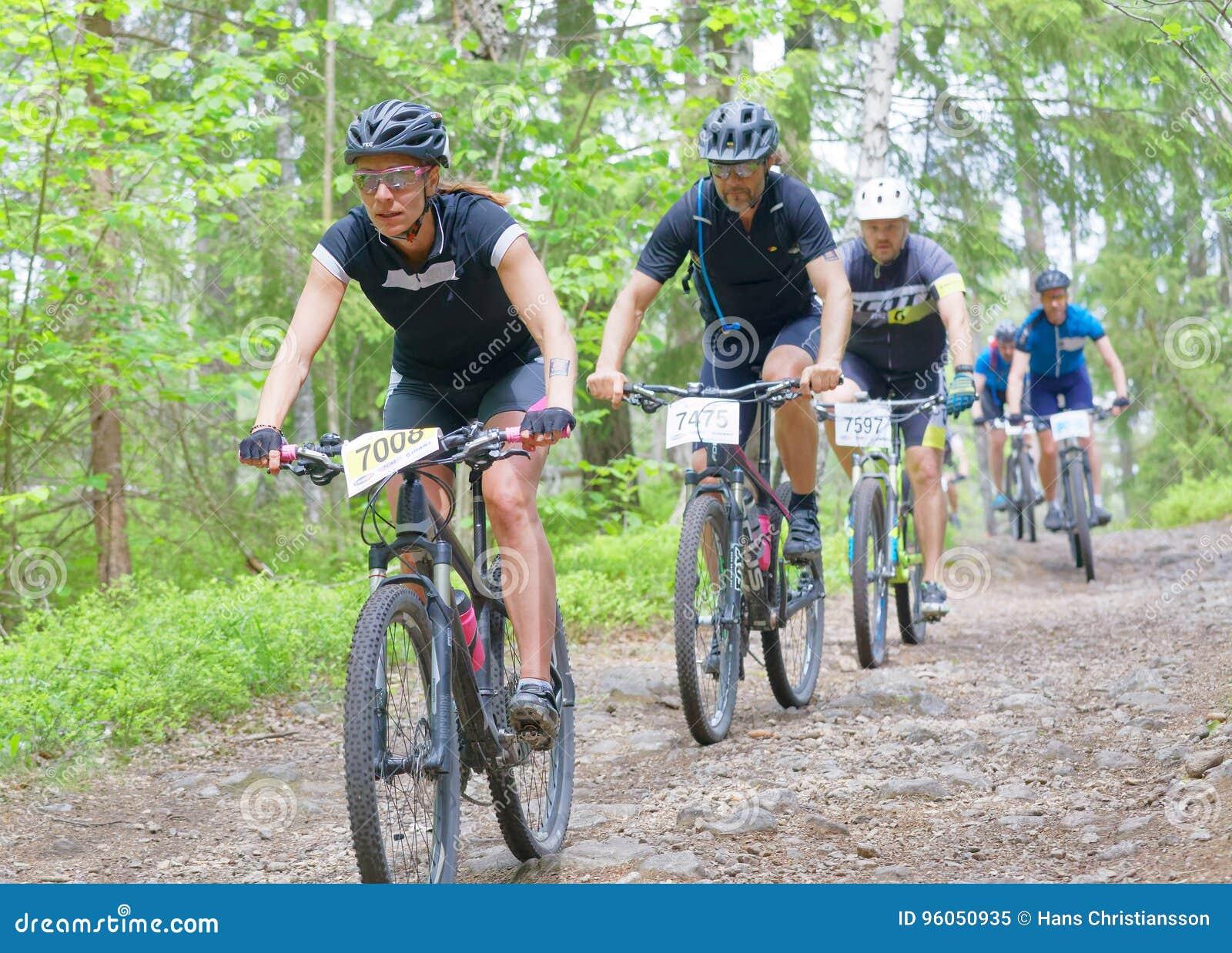 Groupe de cyclistes de vélo de montagne dans la forêt faisant un cycle en descendant