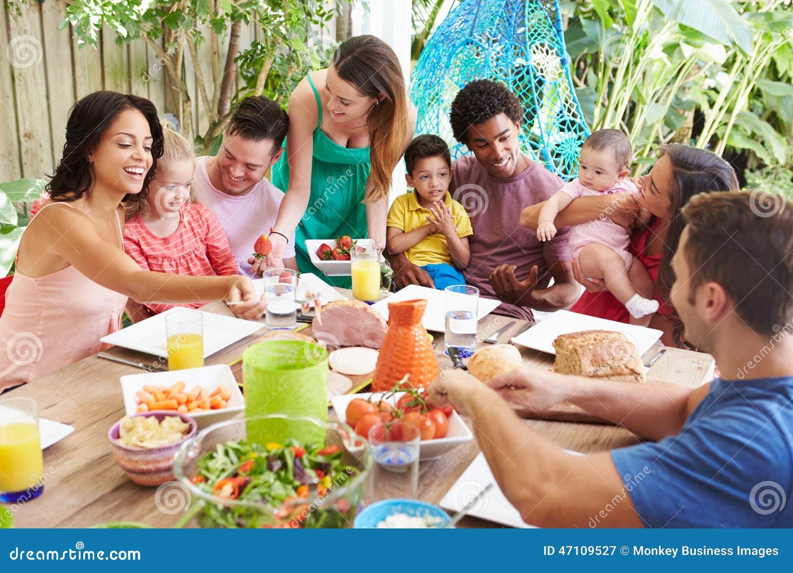Groupe de familles appréciant le repas extérieur à la maison
