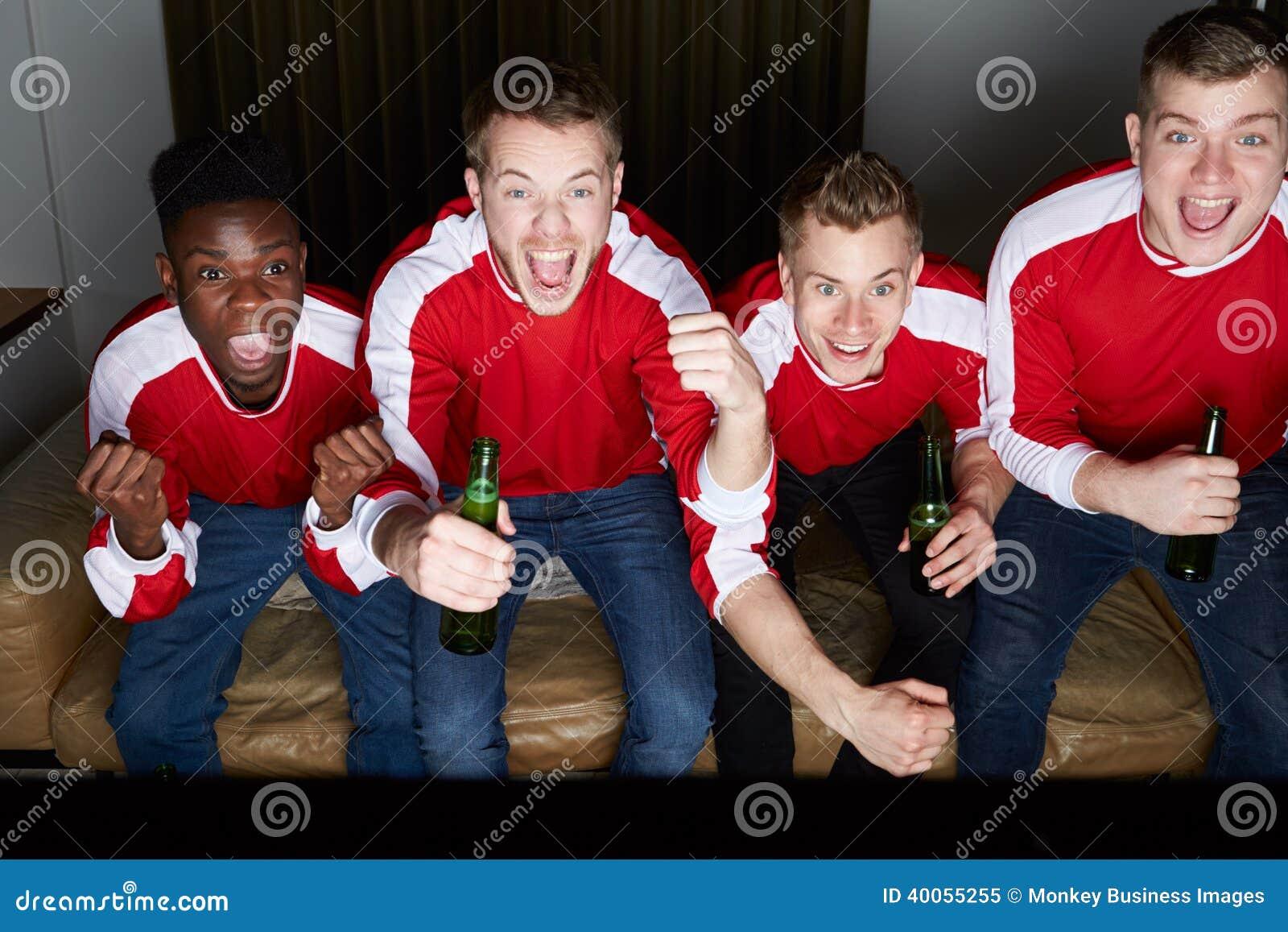 Groupe de fans de sports observant le jeu à la TV à la maison