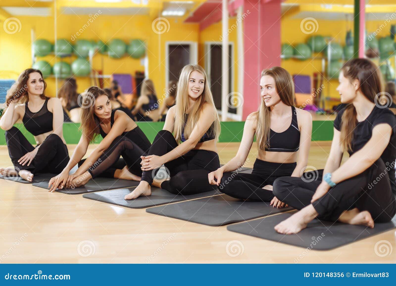 Groupe de femmes heureuses sportives s asseyant sur le plancher de gymnase, étudiants parlant et se reposant après la classe de y