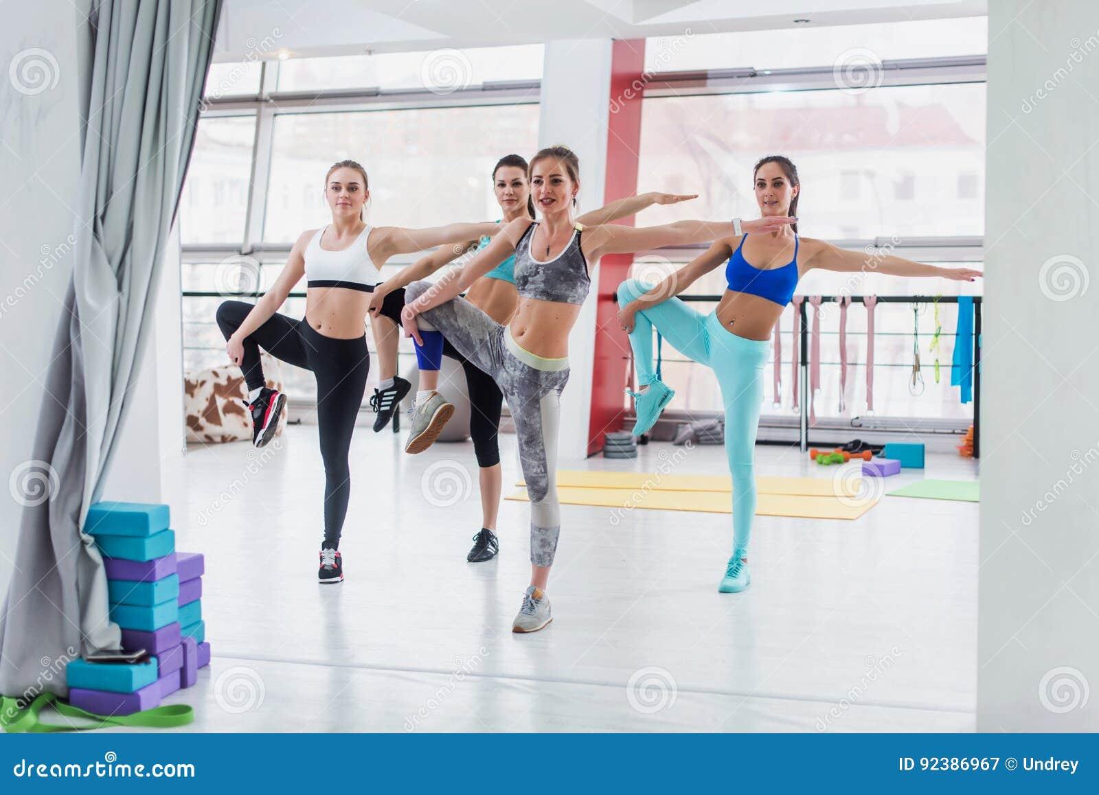 Groupe de filles caucasiennes minces se tenant dans la position d un-jambe pendant la classe de séance d entraînement dans le gym