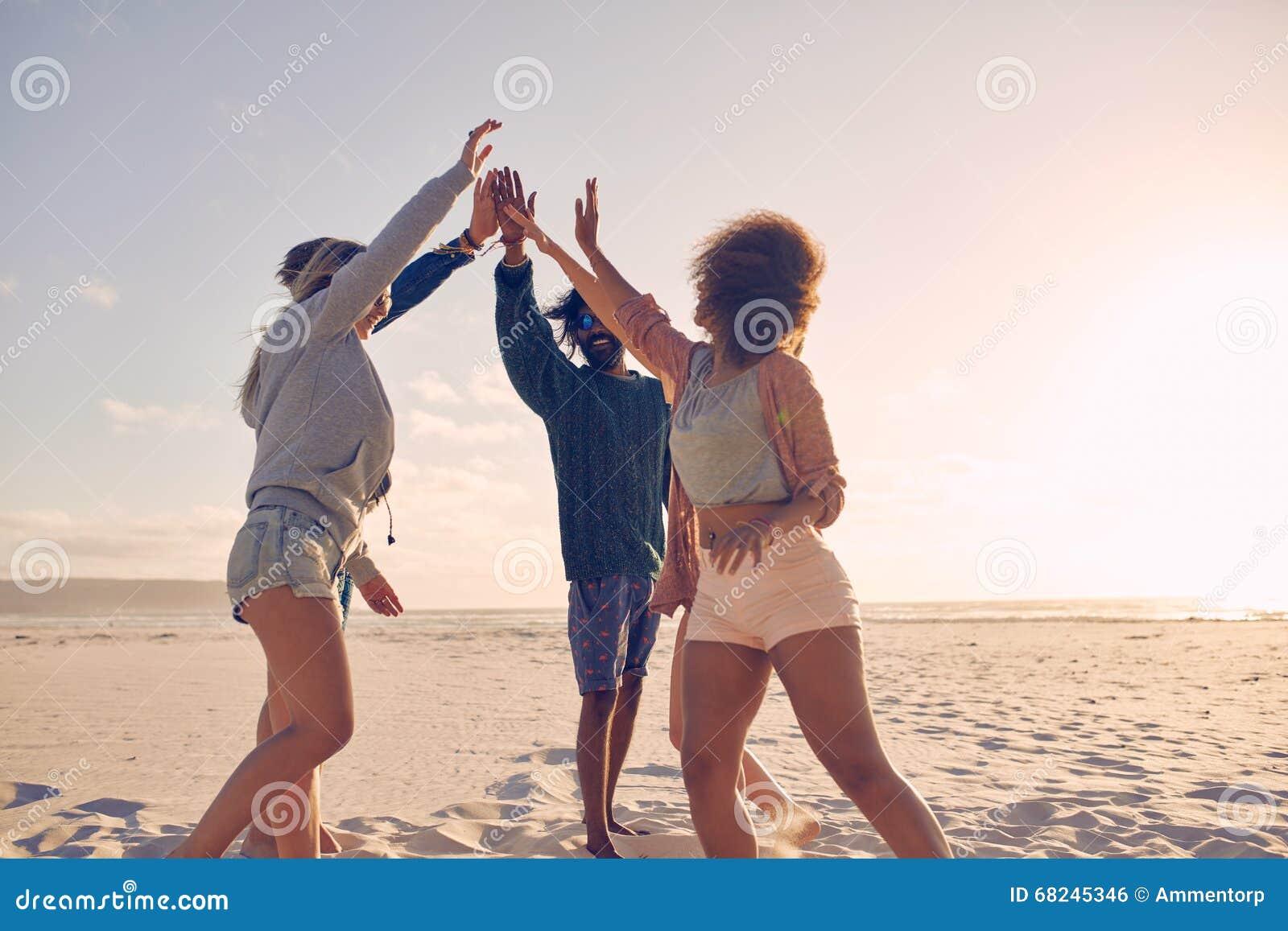 Groupe de fiving élevé d amis heureux sur la plage