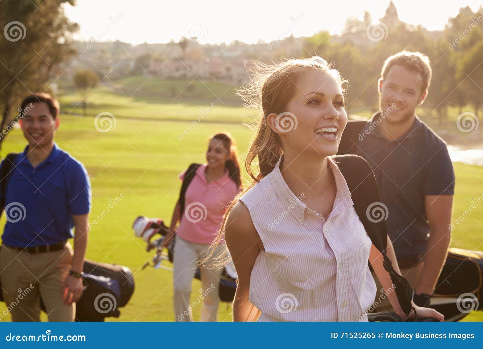 Groupe de golfeurs marchant le long des sacs de golf de transport de fairway