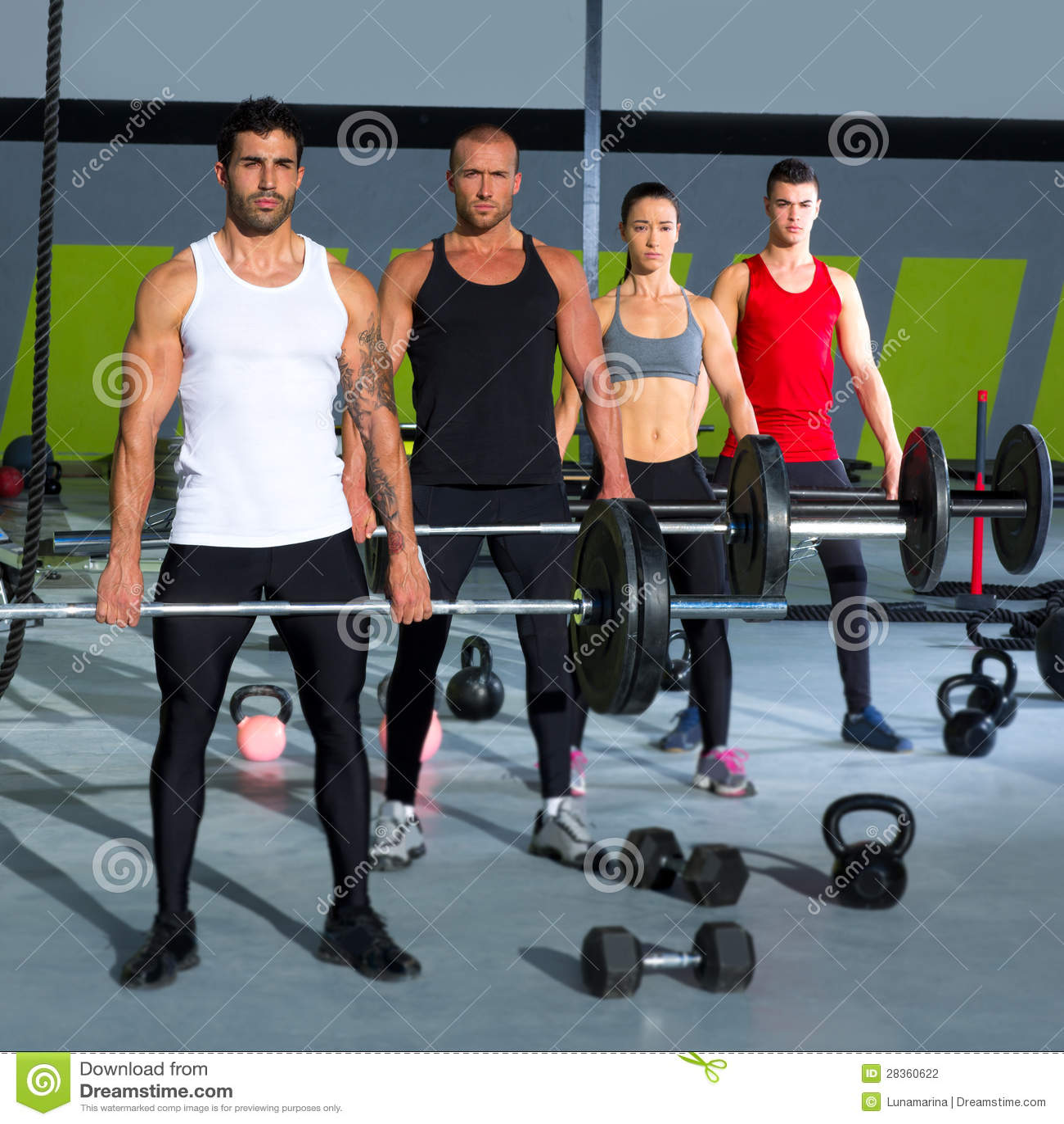 Groupe de gymnase avec la séance d entraînement de crossfit de bar d haltérophilie