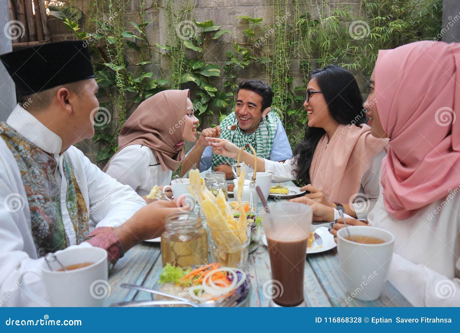 Groupe de jeune musulman heureux dînant extérieur pendant le Ramadan
