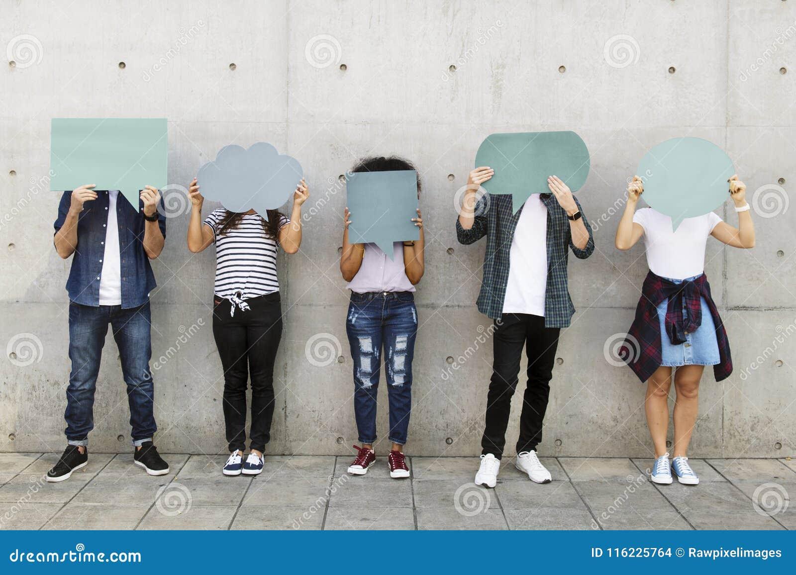Groupe de jeunes adultes tenant dehors le copyspace vide t de plaquette