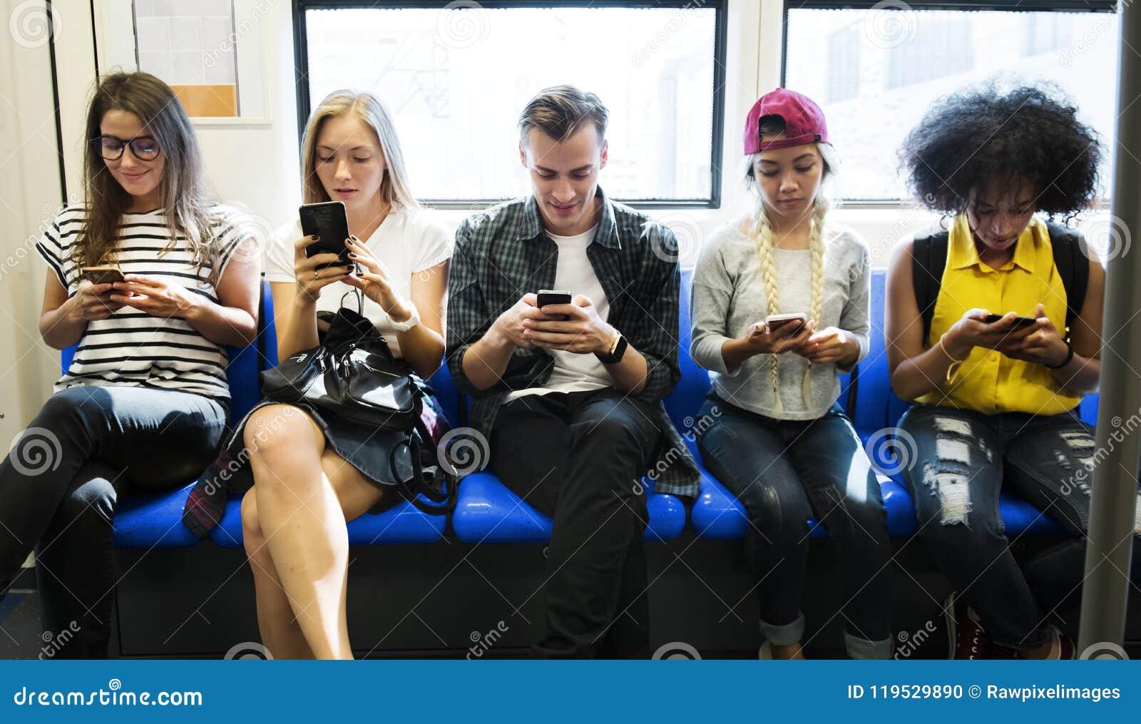 Groupe de jeunes amis adultes à l aide des smartphones dans le souterrain