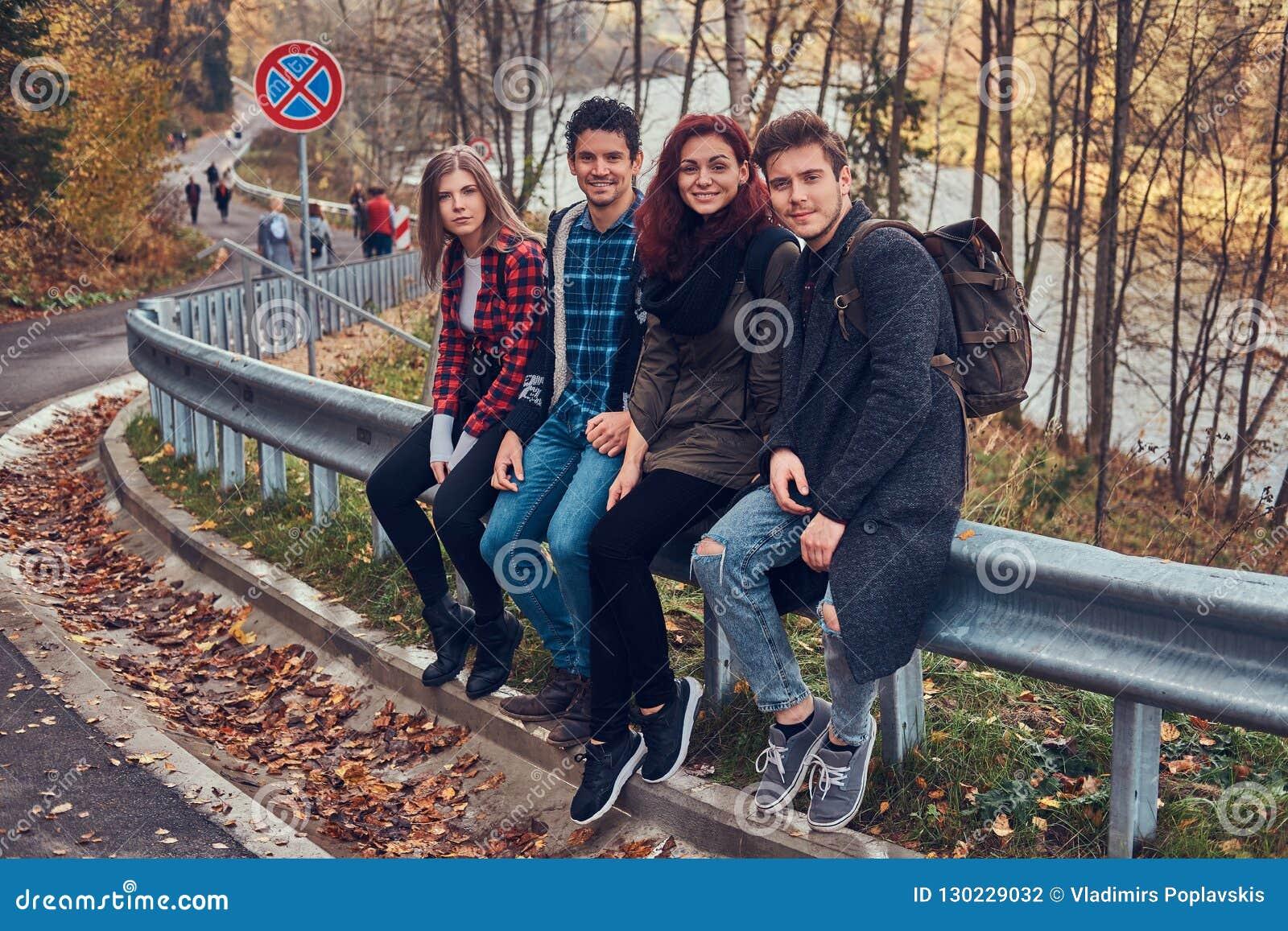 Groupe de jeunes amis avec des sacs à dos se reposant sur la rambarde près de la route avec une belles forêt et rivière à l arriè